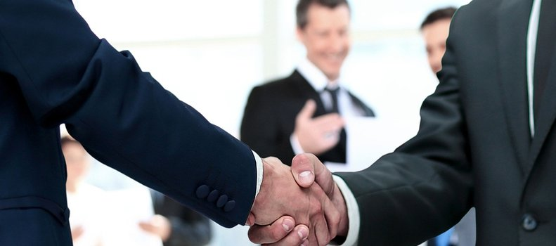 Two men in business suits shaking hands.